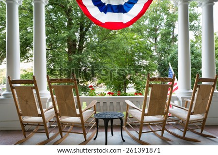 Four vacant wooden rocking chairs lined up on a patio overlooking a lush garden below a draped American flag symbolizing 4th July commemorating Independence Day - stock photo