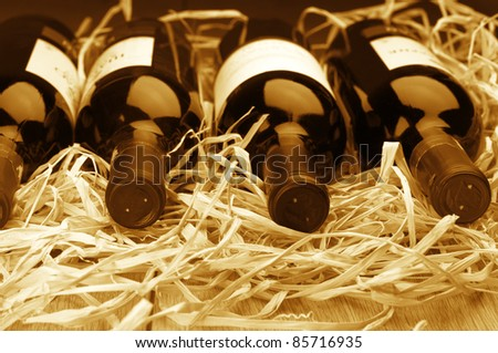 Four various wine bottles lying in row on straw. Monochrome toned image. - stock photo