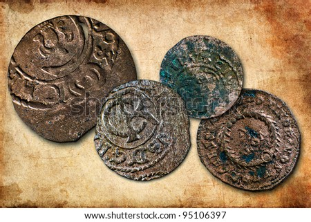 Four very old coins collection on sepia background - stock photo