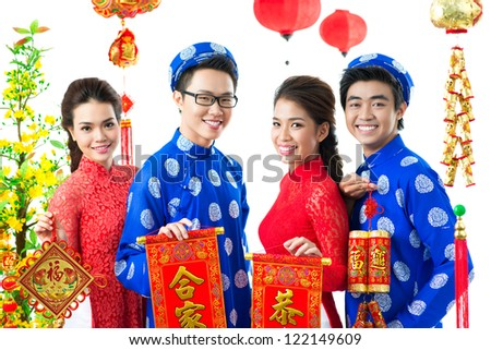 Four Vietnamese showing Tet symbols with traditional greetings - stock photo