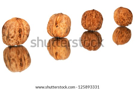 Four walnuts in line with reflection on white