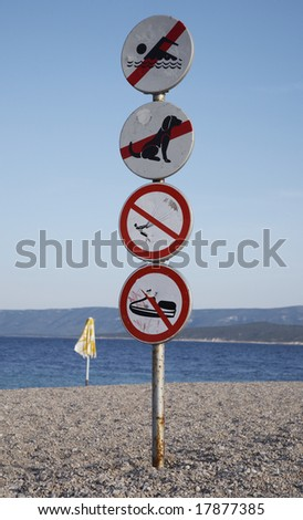 Four warning marks on a beach - stock photo