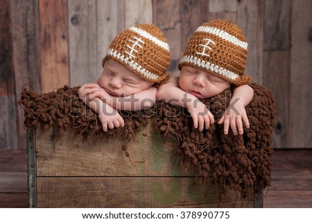 Four week old fraternal, twin, newborn baby boys sleeping in a vintage, wooden crate and wearing football shaped caps. Shot in the studio on a wood background. - stock photo