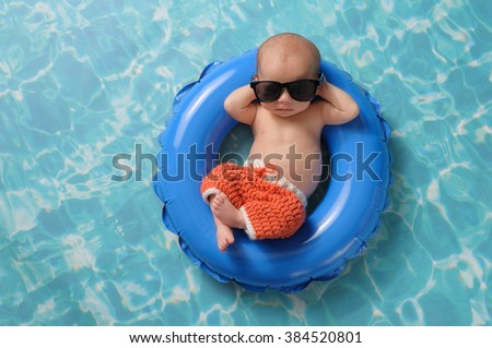 Four week old newborn baby boy sleeping on a tiny inflatable swim ring. He is wearing crocheted board shorts and black sunglasses. - stock photo