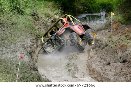 Four wheel drive vehicle coming through a mud and water hazard - stock photo