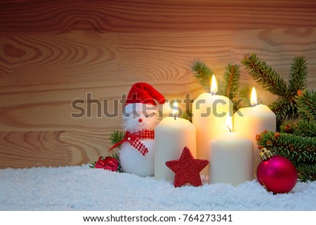 Four white Advent candles burning and Snowman with red Christmas decorations.
