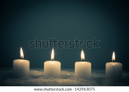 Four white candles on a snowy surface in front of a blue background. - stock photo
