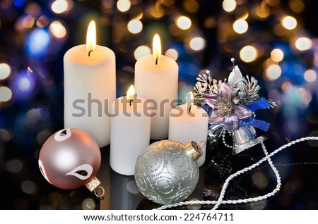 four white lighted candles and Christmas decorations on a bokeh background horizontal - stock photo
