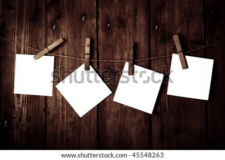four white papers on a wooden background - stock photo