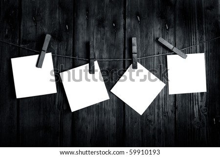 four white papers on a wooden background in black and white - stock photo