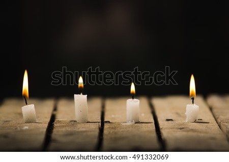 Four white wax candles sitting on wooden surface burning with black background, beautiful light setting