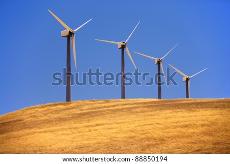 Four windmills in a row. - stock photo