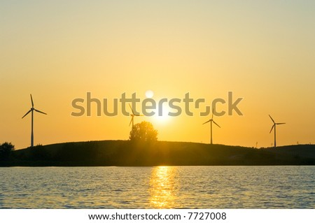 Four windmills lined up on a knoll in front of a blazing sunset