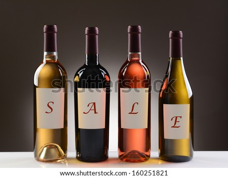 Four Wine Bottles with their labels spelling out the word SALE on a light to dark gray background. Wines include: Cabernet Sauvignon, Chardonnay, Sauvignon Blanc, and White Zinfandel. - stock photo
