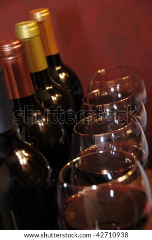 Four wine glasses and four bottles of wine lined up and ready for serving.