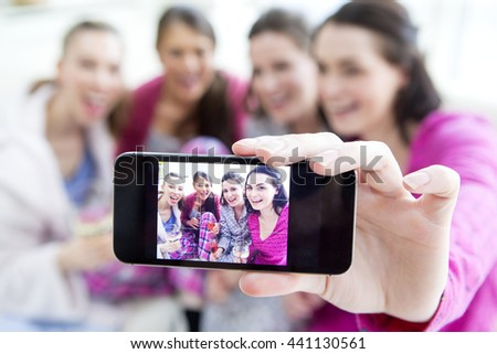 Four woman are sat at home in their pajamas talking a selfie. They are drinking champagne and smiling. - stock photo