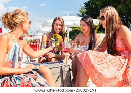 Four woman sitting in beach bar, drinking fancy cocktails and tanning in the sun - stock photo