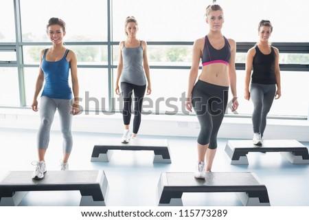 Four women doing aerobics in gym - stock photo
