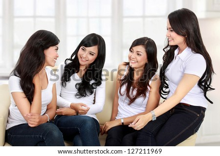 four women friends chatting on the couch at home
