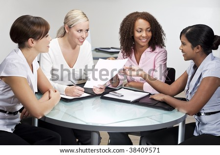 Four women having a business meeting in an office, one African American, one Chinese Asian, One Indian Asian and one Caucasian - stock photo