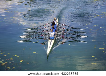 Four women rowing on the tranquil lake - stock photo