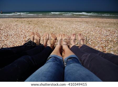 Four women sitting on the brown sandy beach - stock photo