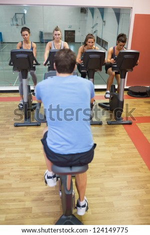 Four women take spinning class at gym - stock photo