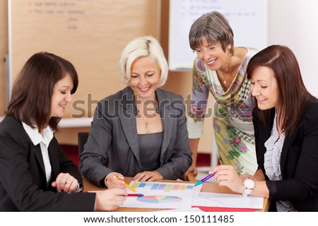 four women working together in a meeting - stock photo