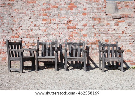 Four wood chairs on a pebbled surface in front of a brick wall.