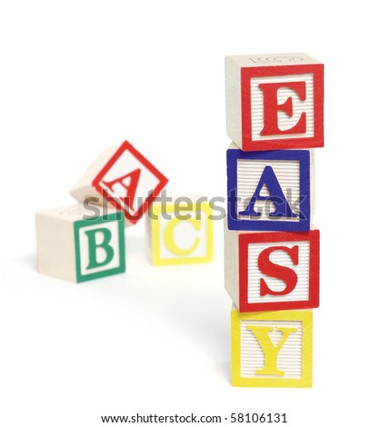 Four wooden alphabet blocks on white background, stacked to form the word, 'easy'. ABC blocks are out of focus in background. Blocks cast shadows.