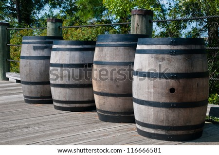 Four wooden barrels along a wooden deck.  Barrels have black metal straps around them.  They are similar to whiskey barrels, but are used for gun powder. - stock photo
