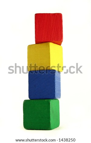 four wooden childrens blocks of different colors stacked in a high tower - low camera angle to emphasize height - stock photo