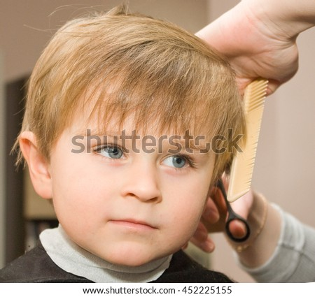 Four y.o.  serious boy with wide opened gray eyes is being haircut by scissors with comb