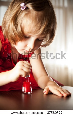 Four-year girl in a red dress with interest paint on nails with nail polish - stock photo