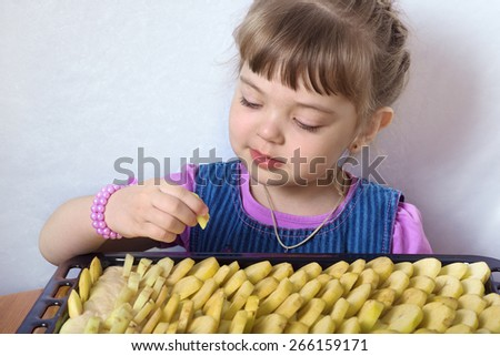 Four-year little girl puts apple slices in apple pie - stock photo