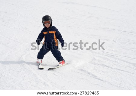 Four year old boy learning to ski alone on the snow, using wedge to stop