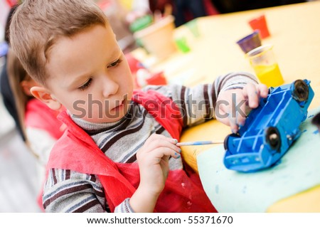 four-year old boy painting a toy car - stock photo