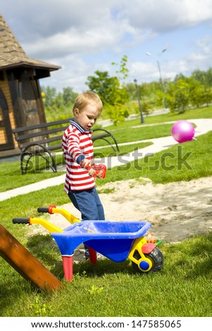 four-year-old boy playing at a playground with sand