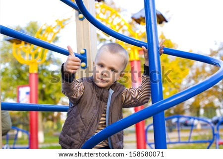Four year old boy playing on the playground in autumn - stock photo