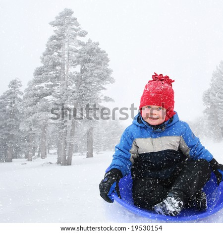 Four year old boy sledding in snowy landscape - stock photo