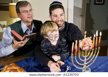 Four year old boy with grandfather and father lighting Hanukkah menorah - stock photo