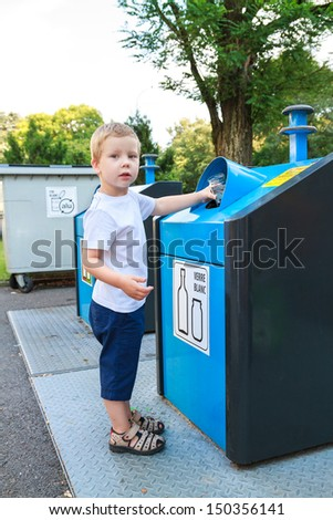 Four year old child putting waste in bin