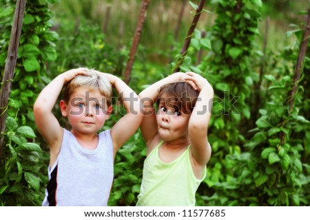 Four year old friends making funny faces among green bean plants in the garden - stock photo