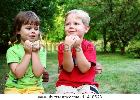 Four year old friends playing in a garden on a beautiful summer day - stock photo