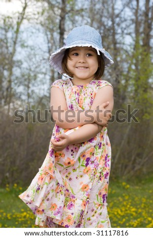 Four year old girl smiling, while wearing a summer dress and enjoying the outside air