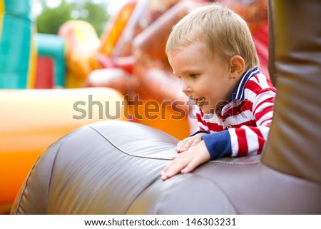 Four-year-old kid playing on a trampoline outdoor