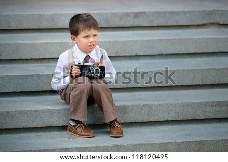 Four years old boy photographing using retro camera - stock photo