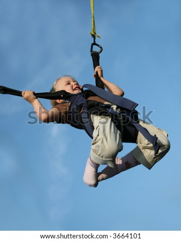 Four years old girl doing mini bungee jumping. - stock photo