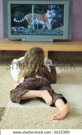 Four years old girl watching tv with remote on cozy carpet. tv screen contains my photographs as well. - stock photo