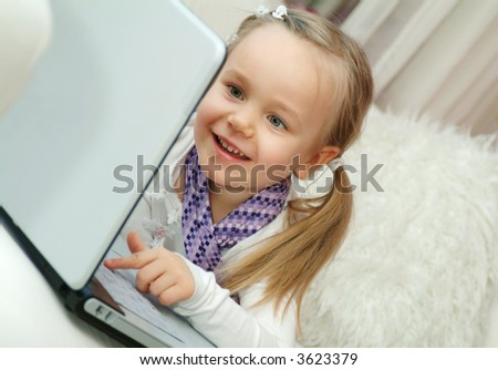 Four years old girl working on laptop with her dad's tie. - stock photo